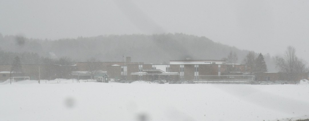 The large 160,000 square foot Stowe Middle High School complex is obscured by falling snow, a very common occurrence in these parts, so near to the Stowe Mountain Resort.