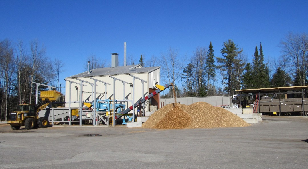New green chips direct from local forest operations are scooped into the screener/re-chipper's feed bin while screened PDCs pile up to the right, waiting to be dried.