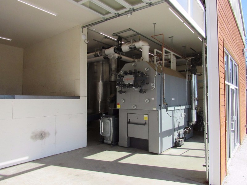 Our Viessmann Vitoflex-300 UF Model KPT-950 that provides heat to the belt dryer has an output of 3.2 million BTUs per hour. It is fired with PDCs loaded into the bin at left.