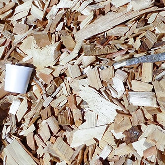green wood chips with a K-cup shown for size comparison