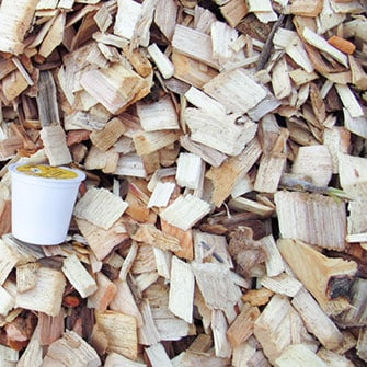 close up of precision dry wood chips with a K-cup shown for size comparison