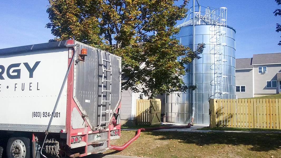 froling energy wood chip truck in the foreground, with hose connected to storage silo